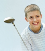 Boy enjoying playing golf outdoors