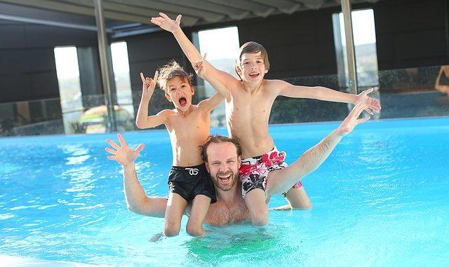 Dad and his boys having fun swimming