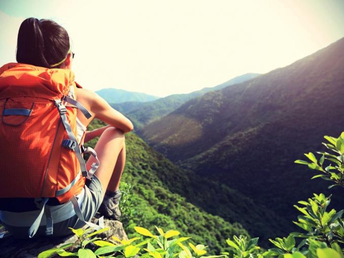 Solo Woman Sitting Looking at a view in the Mountains