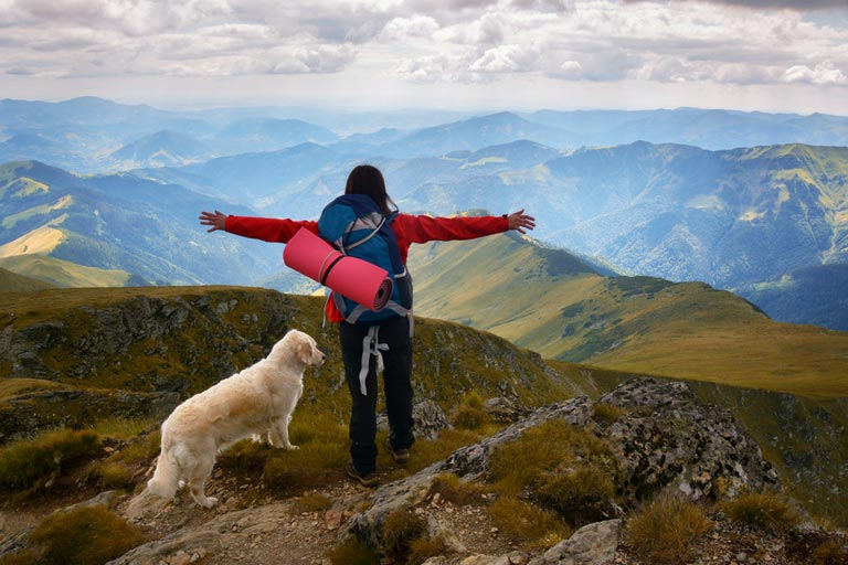 Woman and Dog standing on top of a mountain