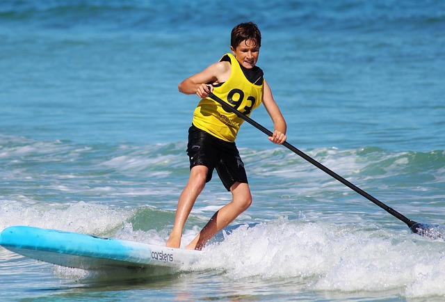 Teen boy on a stand up paddle board in the sea
