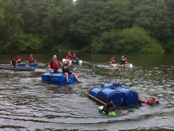 Teams raft racing with one team falling in the water