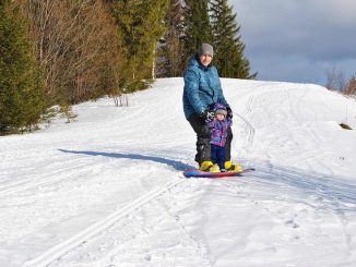 Man and child on a snowboard