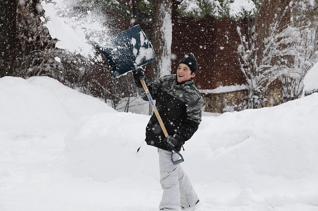 Boy clearing snow with a snow shovel