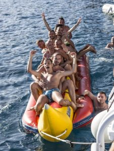 Lads having fun riding an inflatable banana