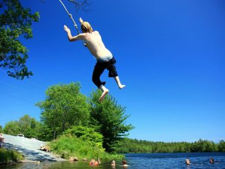 Teen boy jumping off rope swing over water