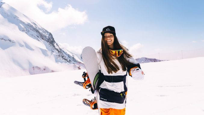 Girl holding a snowboard on the snow