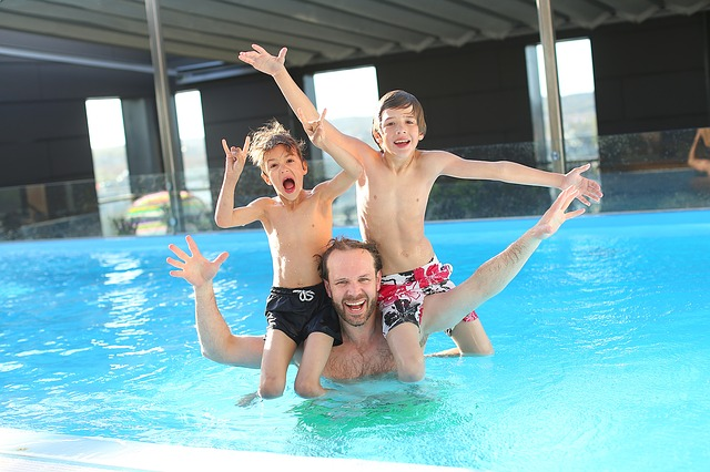 Dad and his boys having fun swimming