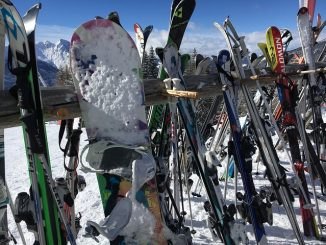 skis and snowboards on a rack while skiers dine at mountaintop restaurant