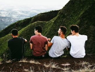 Four guys friends sitting on mountain top