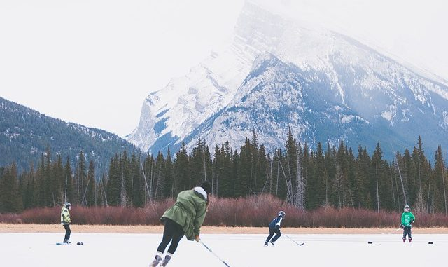 Playing ice hockey outdoors on a lake with the mountains in the background