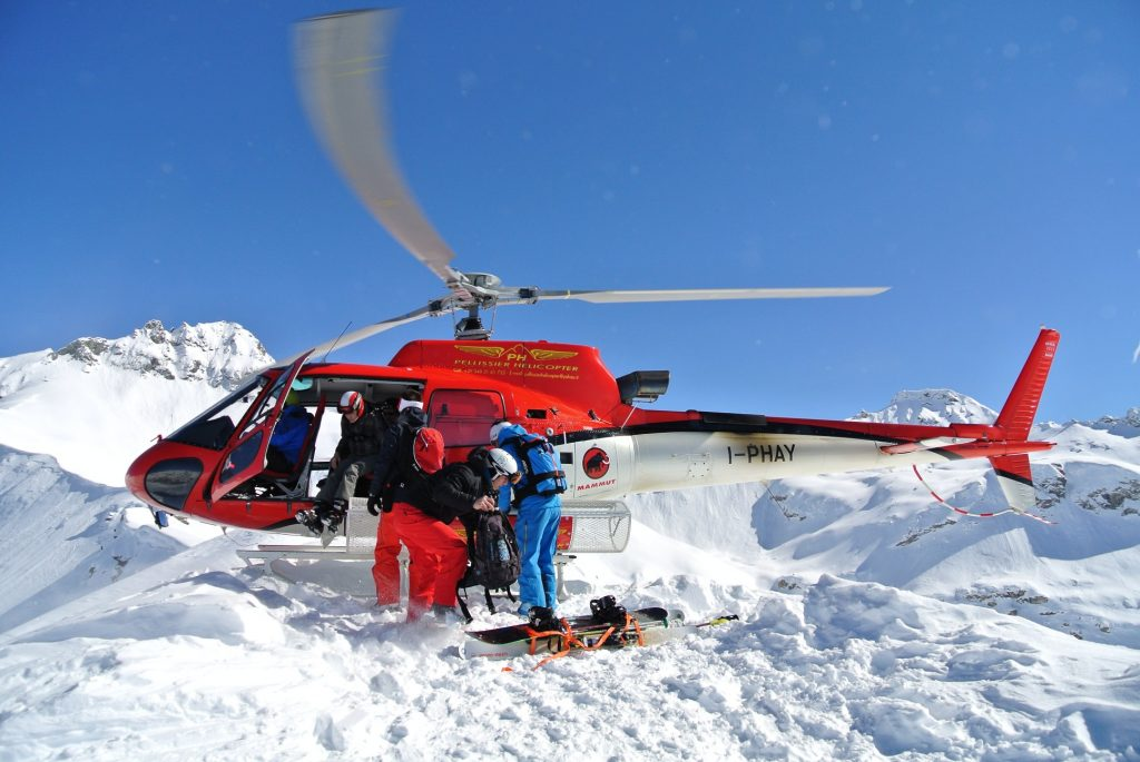 using a helicopter to ski from the top of the mountain