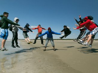 Teens jumping outdoors on the beach