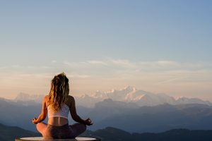 Woman sitting meditating on the top of a mountain
